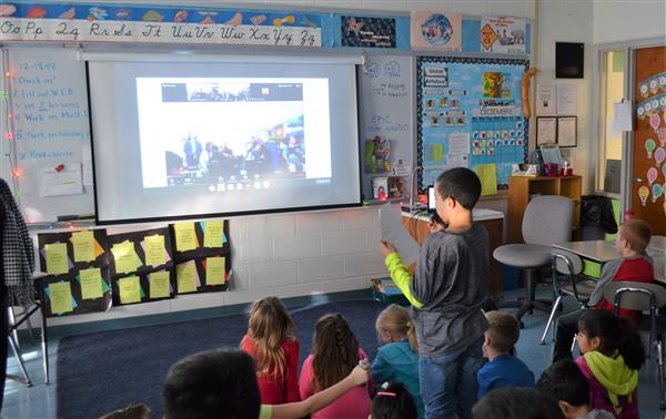 Students asks questions to student on video screen